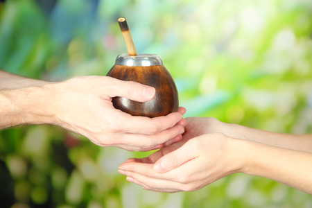 Man hands giving calabash and bombilla with yerba mate, on nature background photo