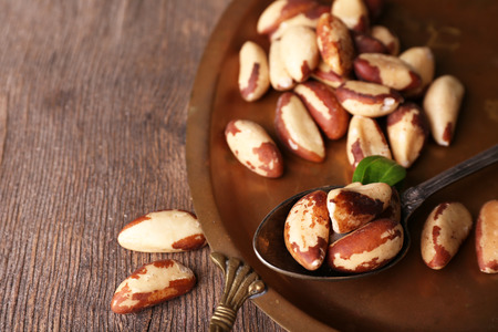 Tasty brasil nuts on salver, on wooden background Stock Photo