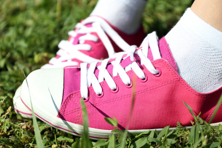 Female legs in sneakers in green grass photo