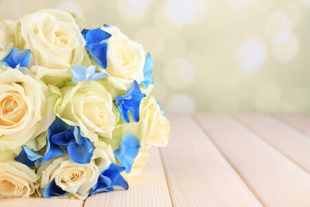Beautiful wedding bouquet with roses on wooden table photo