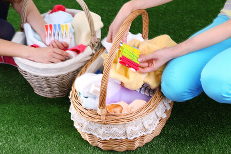 Women holding laundry baskets with clean clothes, towels and pins, on green grass background photo
