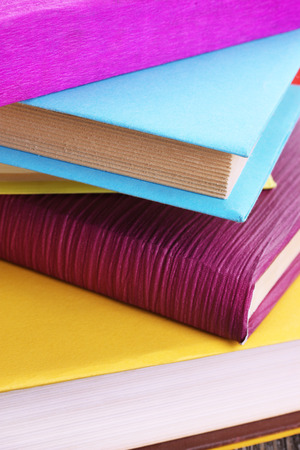 hardback: Stack of colorful hardback and paperback books, close-up