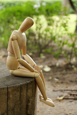 Wooden pose puppet sitting on wooden timber, outdoors photo