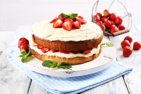 Delicious biscuit cake with strawberries on table on light background Stock Photo