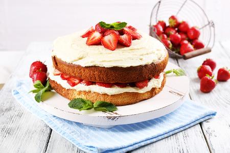 Leckere Keks-Kuchen mit Erdbeeren auf Tabelle auf hellem Hintergrund