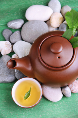 Teapot with dry flowers and herbs ingredients for tea, on stones and color wooden background photo