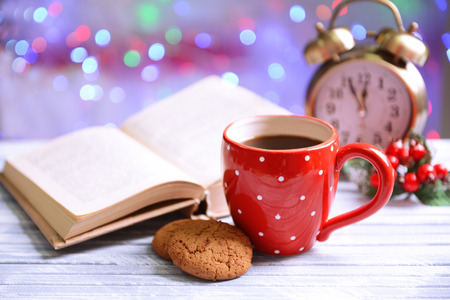 Composition of book with cup of coffee on table on bright background photo