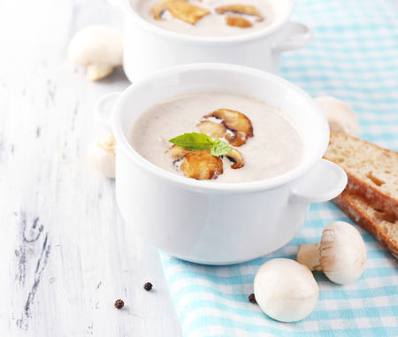 Mushroom soup in white pots, on napkin,  on wooden background Stock Photo - 29675650