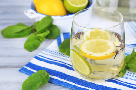 Fresh summer drink with lime and cloves in glass and jug, on color wooden background photo