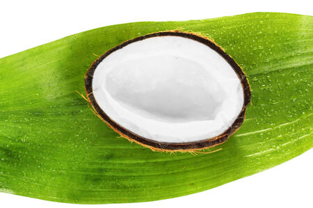 half coconut with green leaf on white background close-up photo