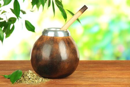 mate infusion: Calabash and bombilla with yerba mate on wooden table, on natural background Stock Photo