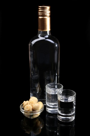 Bottle of vodka  and glasses, marinated mushrooms isolated on black photo