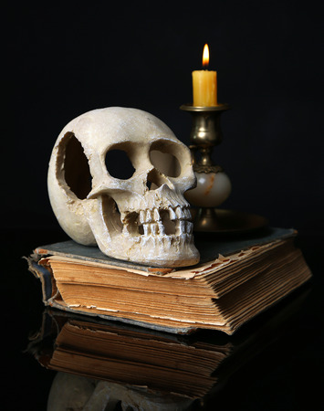 Skull and candle on old book isolated on black photo