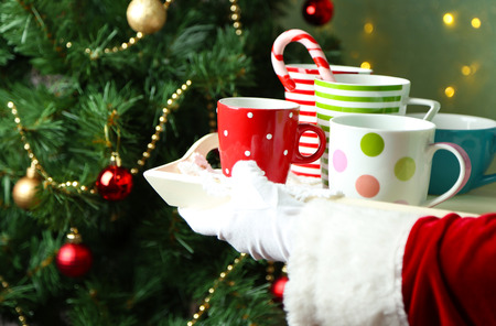 Santa holding  tray with mugs in his hand, on bright background photo