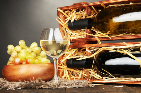 bordeau: Wooden case with wine bottles, wineglass and grape on wooden table on grey background Stock Photo