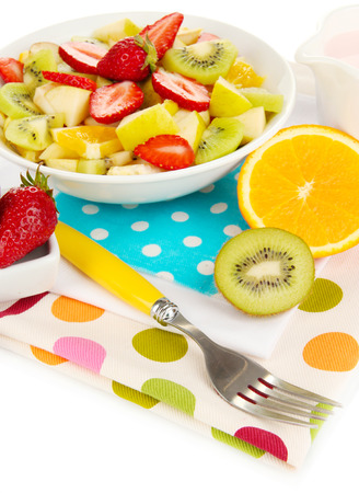 Useful fruit salad of fresh fruits and berries in bowl isolated on white photo