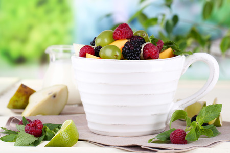 Fruit salad in cup on wooden table on nature background photo
