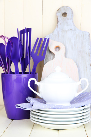 housewares: Plastic kitchen utensils in cup on wooden table Stock Photo