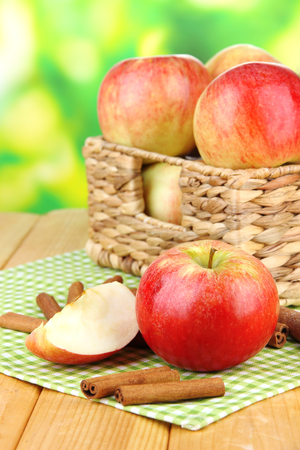 Ripe apples with with cinnamon sticks  on  wooden table, on bright background photo