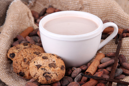 Cocoa drink and cocoa beans on sackcloth  background photo