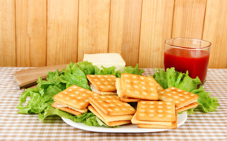 Sandwich crackers with cheese and tomato juice on tablecloth on wooden background photo