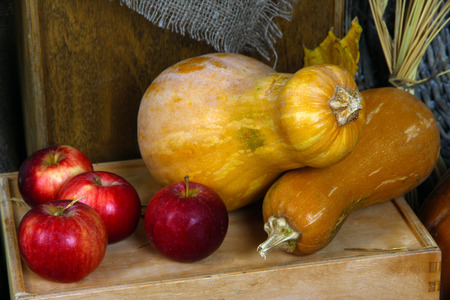 Pumpkins and apples on crate close up photo