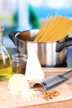 Process of preparing pasta. Composition with row spaghetti in pan, grater, cheese, on wooden table  on bright background photo