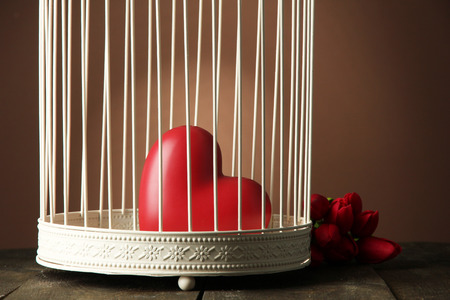 prisoner of love: Heart in decorative cage on wooden table, on brown background
