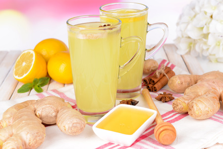 Healthy ginger tea with lemon and honey on table on light background photo
