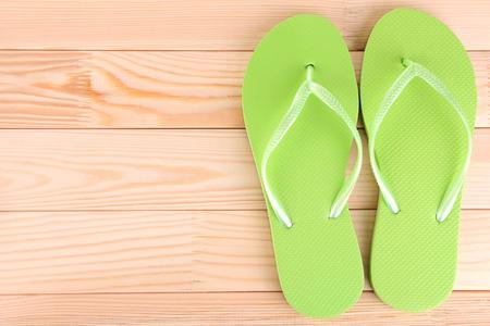 Bright flip-flops on wooden background photo
