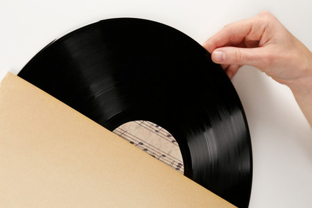 Hands opening old vinyl record, isolated on white photo