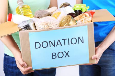 Volontari con scatola di donazione con i prodotti alimentari su sfondo grigio Archivio Fotografico