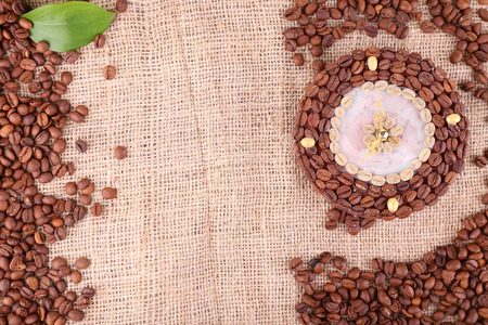 Beautiful clock of coffee beans, on burlap background photo
