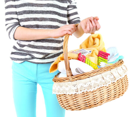 Woman holding laundry basket with clean clothes, towels and pins, isolated on white photo