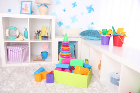 Colorful plastic toys in children room photo