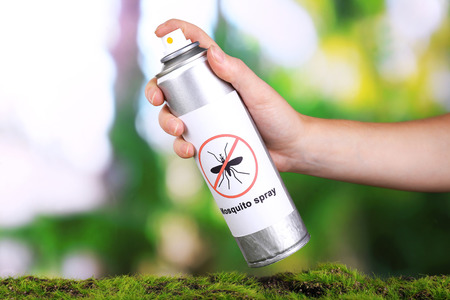 Hand holding mosquito spray on nature background photo
