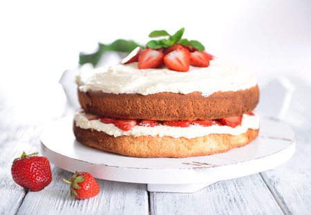 Delicious biscuit cake with strawberries on table on light background photo