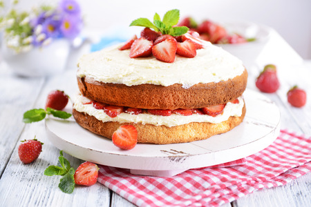Delicious biscuit cake with strawberries on table close-up photo
