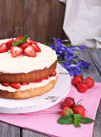 Delicious biscuit cake with strawberries on table on wooden background photo