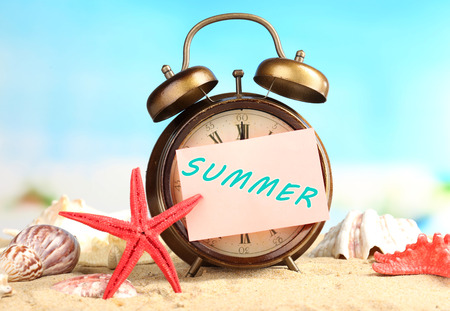 Summertime. Old clock on sand  photo
