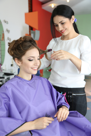 Young woman hairdresser do hairstyle girl in beauty salon