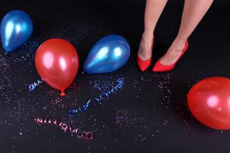 the aftermath: Legs with confetti and balloons on the floor Stock Photo