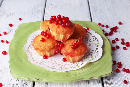 Tasty muffin with red currant berries on plate, on color wooden background photo