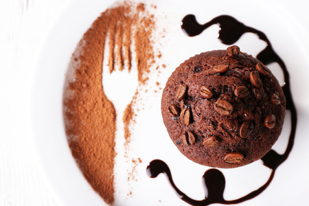 Chocolate muffin with chocolate sauce on plate, on wooden background photo