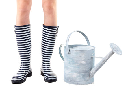 Young woman in rubber boots with watering can, isolated on white photo