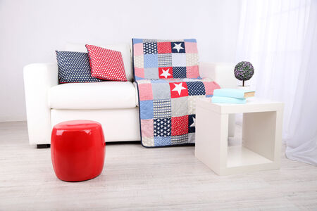 White couch with multicolor pillows and plaid in modern living room photo