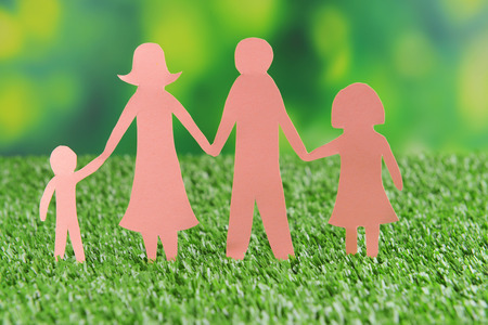 Paper family on green grass, close up photo