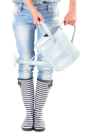 Young woman in rubber boots holding watering can, isolated on white photo