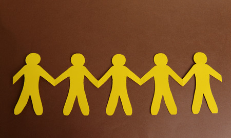 Paper people on brown background photo