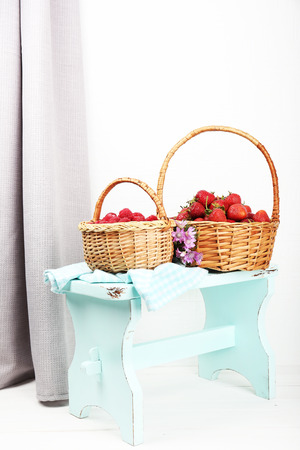 Fresh berries in baskets on white wall background photo